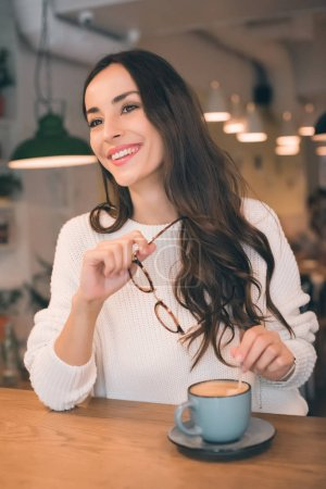 cheerful young woman holding eyeglasses while sitting at table with coffee cup in cafe