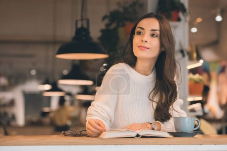 attractive woman reading book at table with coffee cup in cafe