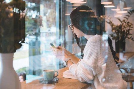 Photo pour Vue latérale de la jeune femme à lunettes à l'aide de smartphone à table avec une tasse de café en café - image libre de droit