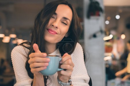 portrait of young woman with closed eyes enjoying coffee at table in cafe