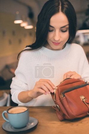 attractive woman pulling out cash from bag at table with coffee cup in cafe