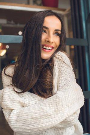 Foto de Enfoque selectivo de feliz hermosa mujer mirando lejos en café - Imagen libre de derechos