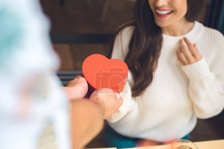 cropped image of man presenting heart shaped gift box to happy girlfriend at table in cafe