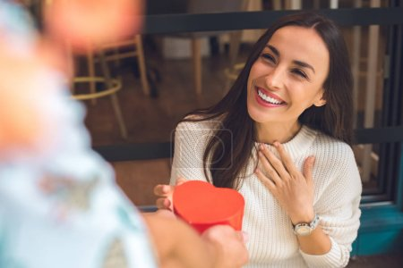 cropped image of man presenting heart shaped gift box to smiling girlfriend gesturing by hand at table in cafe