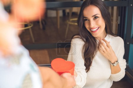 partial view of man presenting heart shaped gift box to happy girlfriend at table in cafe