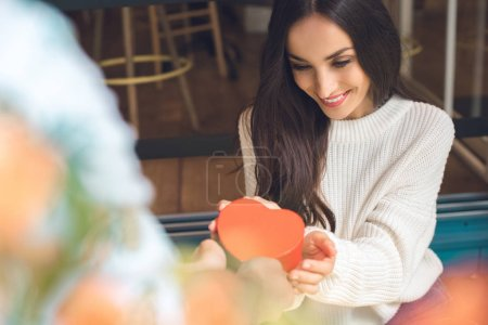 cropped image of man presenting heart shaped gift box to attractive young girlfriend at table in cafe