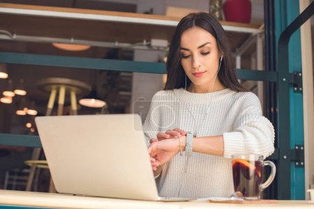 Photo for Young female freelancer in earphones checking wristwatch at table with laptop and mulled wine in cafe - Royalty Free Image
