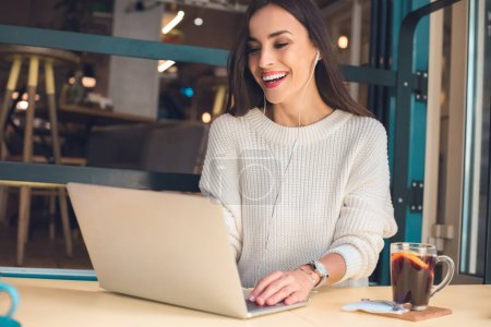 Photo for Laughing female freelancer in earphones working on laptop at table with mulled wine in cafe - Royalty Free Image