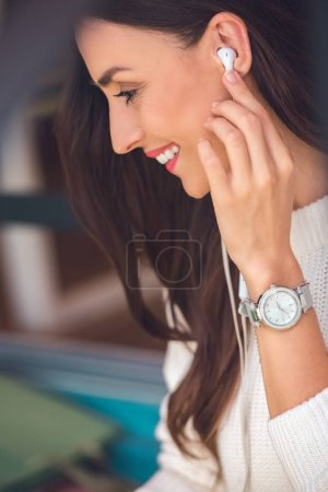 selective focus of smiling young woman putting on earphones in cafe