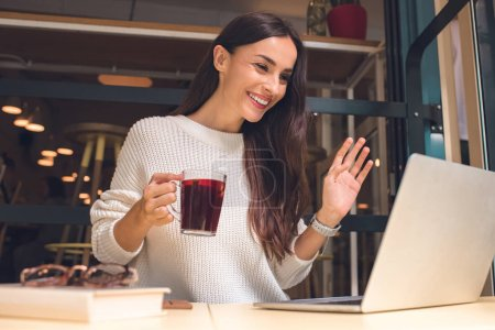 happy young woman holding cup of mulled wine and waving by hand while having video call on laptop at table in cafe