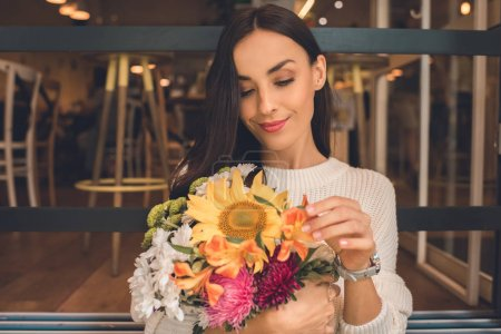 beautiful young woman holding colorful bouquet from various flowers in cafe