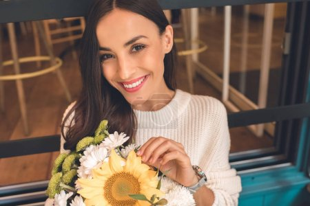 portrait of smiling young woman holding colorful bouquet from various flowers and looking at camera in cafe