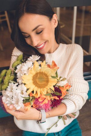 smiling young woman holding colorful bouquet from various flowers in cafe