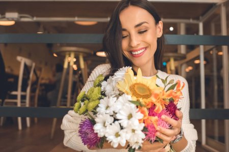 selective focus of happy young woman holding colorful bouquet from various flowers in cafe