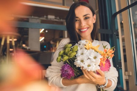 portrait of smiling young woman holding colorful bouquet from various flowers in cafe