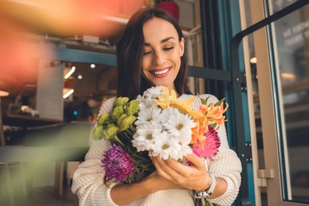 selective focus of young woman holding colorful bouquet from various flowers in cafe