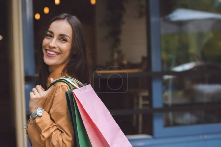 Photo for Portrait of stylish beautiful woman with shopping bags over shoulder looking away at city street - Royalty Free Image
