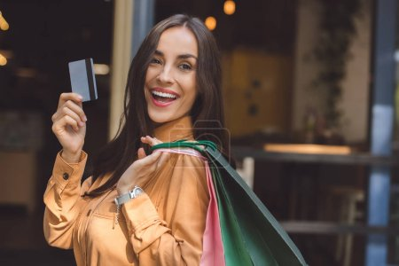 Photo for Laughing fashionable woman with shopping bags showing credit card at city street - Royalty Free Image