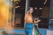 """Постер, картина, фотообои """"выборочный фокус счастливым стильный молодой женщины с сумки говорить на смартфоне на городской улице"""""""