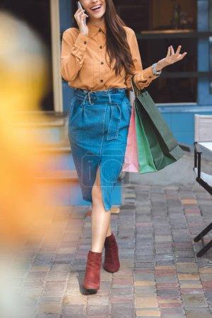 Photo pour Vue partielle de l'élégant shopper femelle avec sacs à provisions parler sur smartphone à la ville de rue - image libre de droit