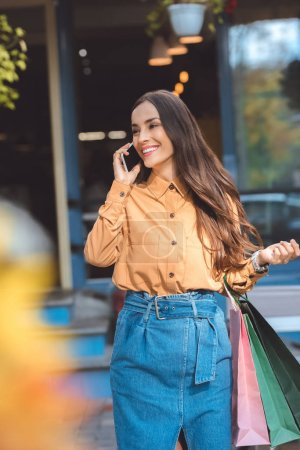 Photo pour Heureuse jeune femme élégante avec sacs à provisions parler sur smartphone à la ville de rue - image libre de droit