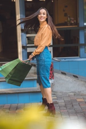happy stylish young woman turning around with shopping bags at city street