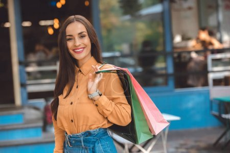 Photo for Portrait of smiling stylish female shopper with shopping bags at city street - Royalty Free Image