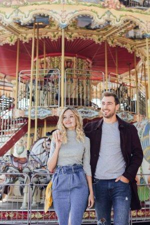 Photo pour Couple affectueux en automne tenue étreindre près du carrousel en parc d'attractions - image libre de droit