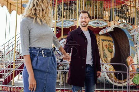 Foto de Pareja cariñosa en traje de otoño cogidos de la mano cerca de carrusel en el parque de atracciones y mirando el uno al otro - Imagen libre de derechos