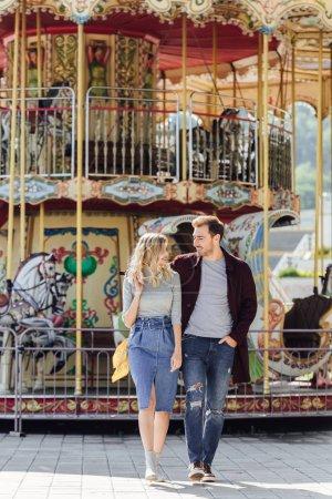 Foto de Pareja cariñosa en traje de otoño caminando cerca de carrusel en el parque de atracciones y mirando el uno al otro - Imagen libre de derechos