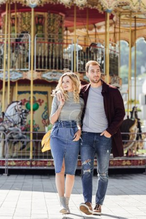 affectionate couple in autumn outfit walking and hugging near carousel in amusement park