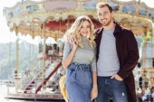 smiling affectionate couple in autumn outfit cuddling near carousel in amusement park and looking at camera