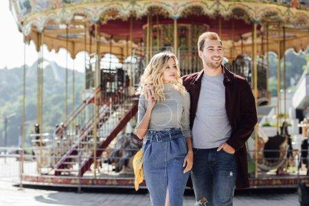 Photo pour Couple hétérosexuel en tenue d'automne de marche et les câlins près du carrousel en parc d'attractions - image libre de droit
