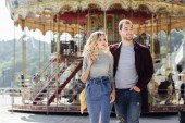 heterosexual couple in autumn outfit walking and cuddling near carousel in amusement park