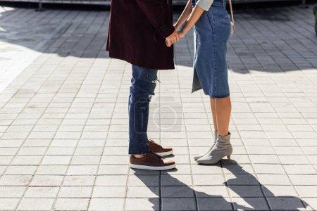 Foto de Imagen recortada de la pareja en traje de otoño cogidos de la mano en la calle en la ciudad de - Imagen libre de derechos