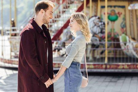 Foto de Pareja cariñosa en traje de otoño cogidos de la mano y mirando el uno al otro cerca de carrusel en el parque de atracciones - Imagen libre de derechos