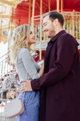 side view of affectionate couple in autumn outfit cuddling near carousel in amusement park