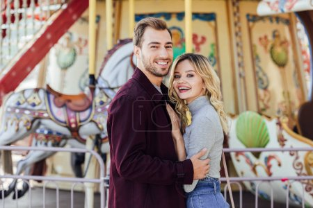 happy affectionate couple in autumn outfit cuddling near carousel in amusement park and looking at camera