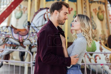 side view of romantic couple in autumn outfit cuddling near carousel in amusement park