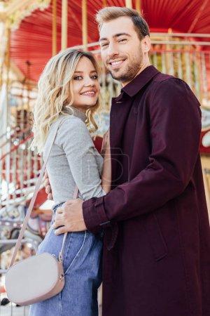 Photo pour Smiling couple élégant câlins près du carrousel en parc d'attractions et de regarder la caméra - image libre de droit