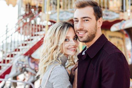 Foto de Retrato de sonriente pareja cariñosa en traje de otoño mirando a cámara junto a carrusel en el parque de atracciones - Imagen libre de derechos
