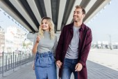 romantic smiling couple in autumn outfit holding hands and walking under bridge in city