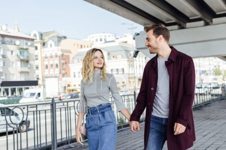 Photo for Romantic couple in autumn outfit holding hands and looking at each other under bridge in city - Royalty Free Image