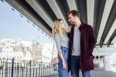tender couple in autumn outfit looking at each other under bridge in city