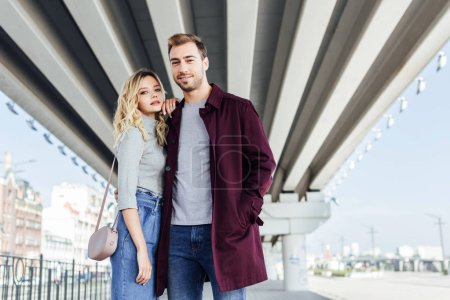 stylish couple in autumn outfit hugging under bridge in city and looking at camera