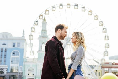 Photo for Side view of couple in autumn outfit holding hands with observation wheel on background - Royalty Free Image