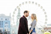 side view of couple in autumn outfit holding hands with observation wheel on background