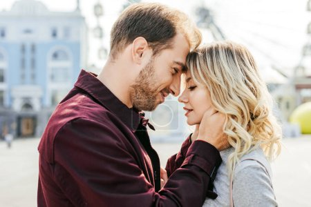 Photo for Side view of couple in autumn outfit touching with foreheads in city - Royalty Free Image