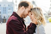 side view of couple in autumn outfit touching with foreheads in city