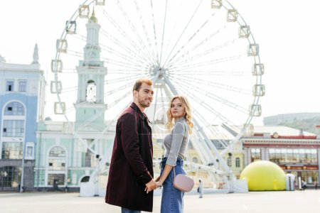 side view of couple in autumn outfit holding hands with ferris wheel on background